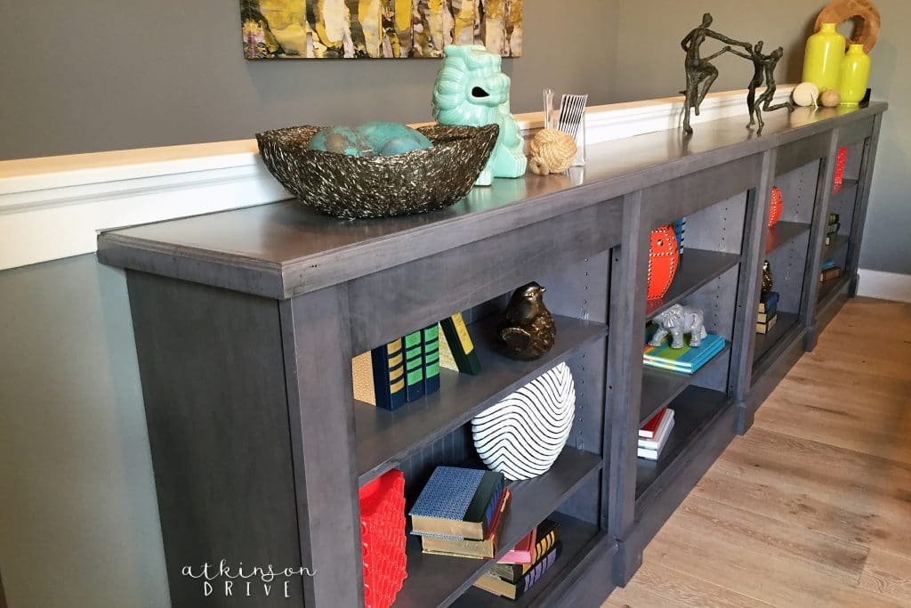 Line a half wall at the top of the stairs with book cases. Decorate with vintage books and pretty nic-nacs
