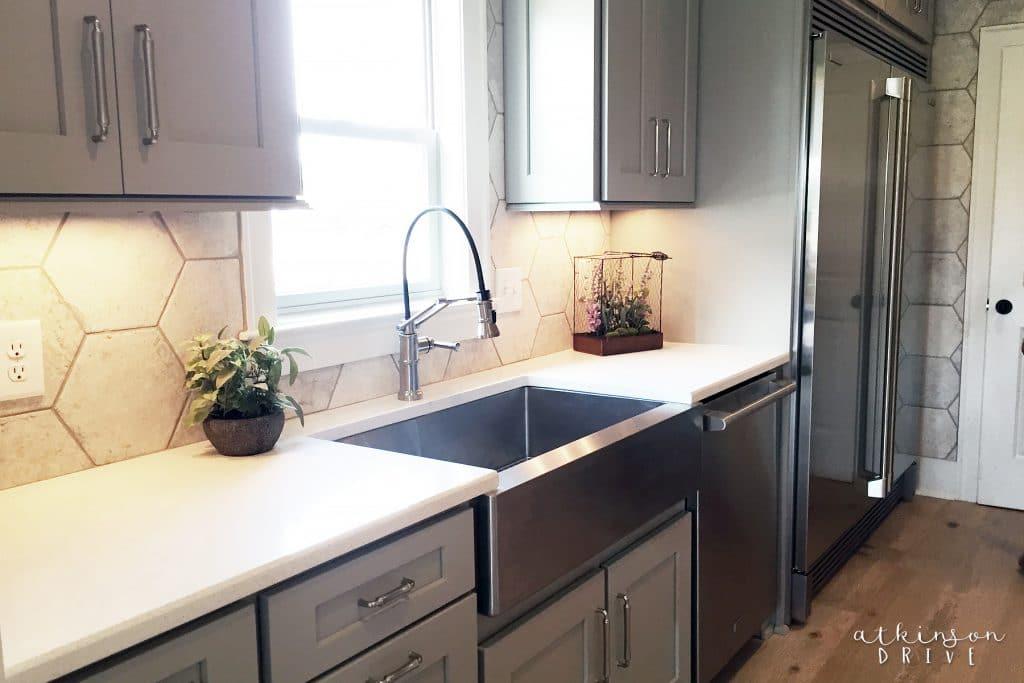 This modern farmhouse kitchen boasts a single-basin metal sink and a restaurant size fridge / freezer!