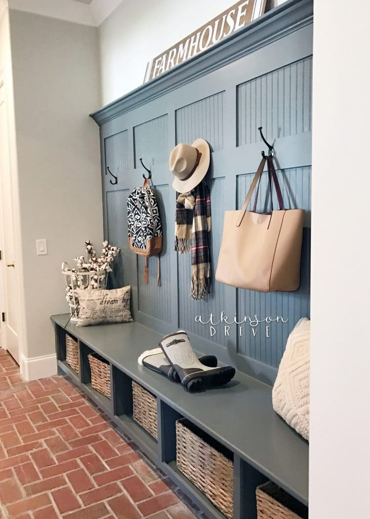 Mud room farmhouse storage bench with hooks and a brick floor /// Woodridge Parade of Homes Tour by Atkinson Drive