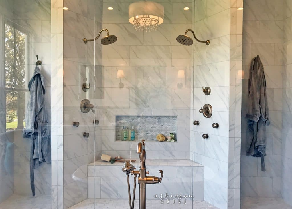 Giant marble master bathroom shower with bench and two shower heads /// Woodridge Parade of Homes Tour by Atkinson Drive