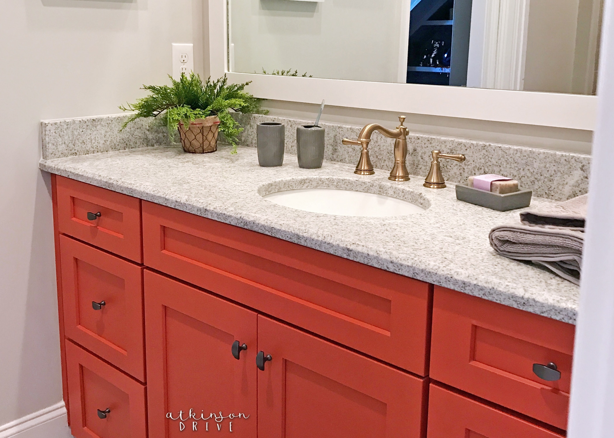 Bathroom with bright coral shaker style cabinets and bronze accents /// Woodridge Home Tour by Atkinson Drive