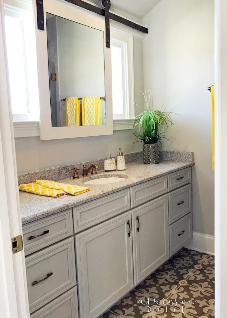 Whimsical girl's bathroom with bold floor tiles and a sliding mirror /// Woodridge Parade of Homes Tour by Atkinson Drive