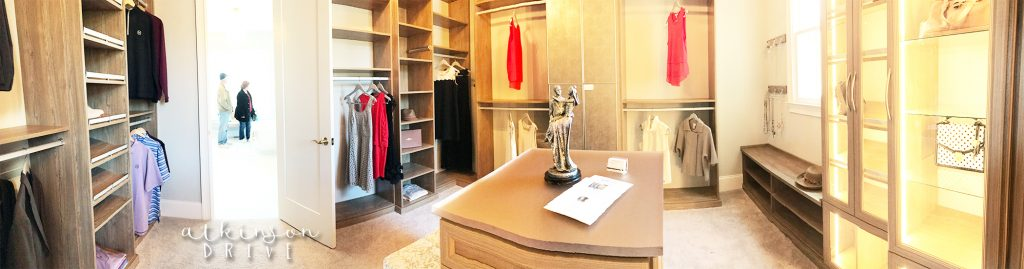 Master bedroom closet with a storage island, and lights in the cabinets /// Woodridge Home Tour by Atkinson Drive