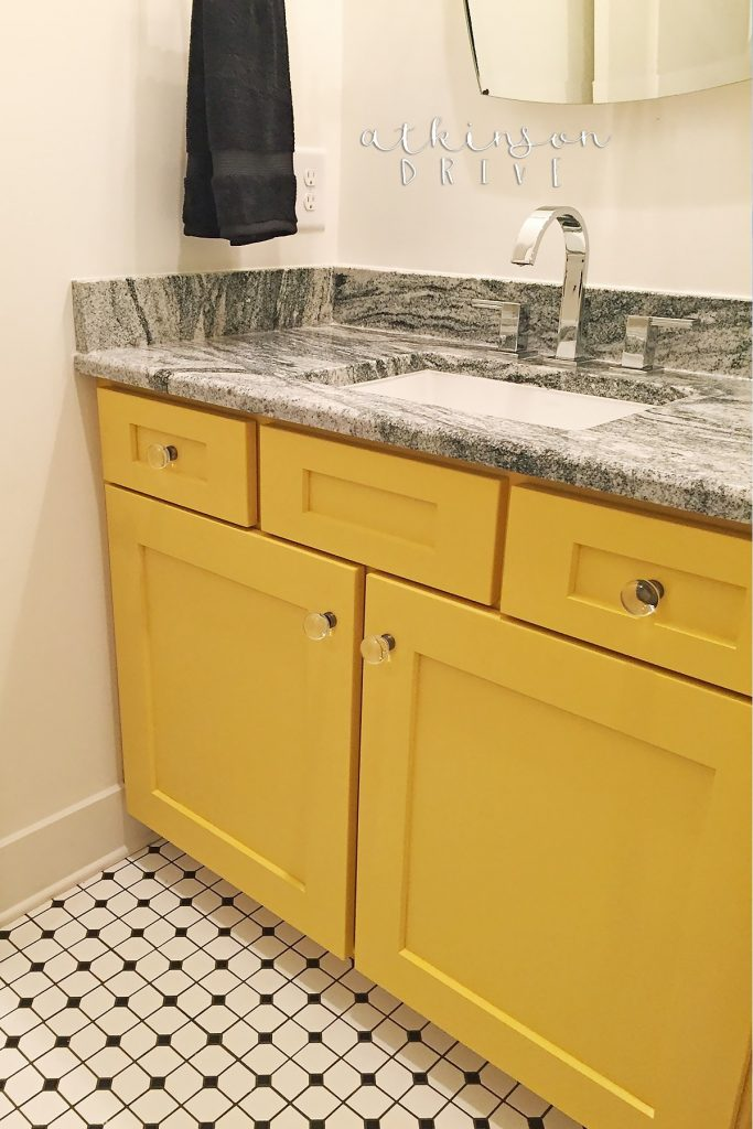Kids bathroom featuring yellow cabinets and black and white vintage-inspired tile floors