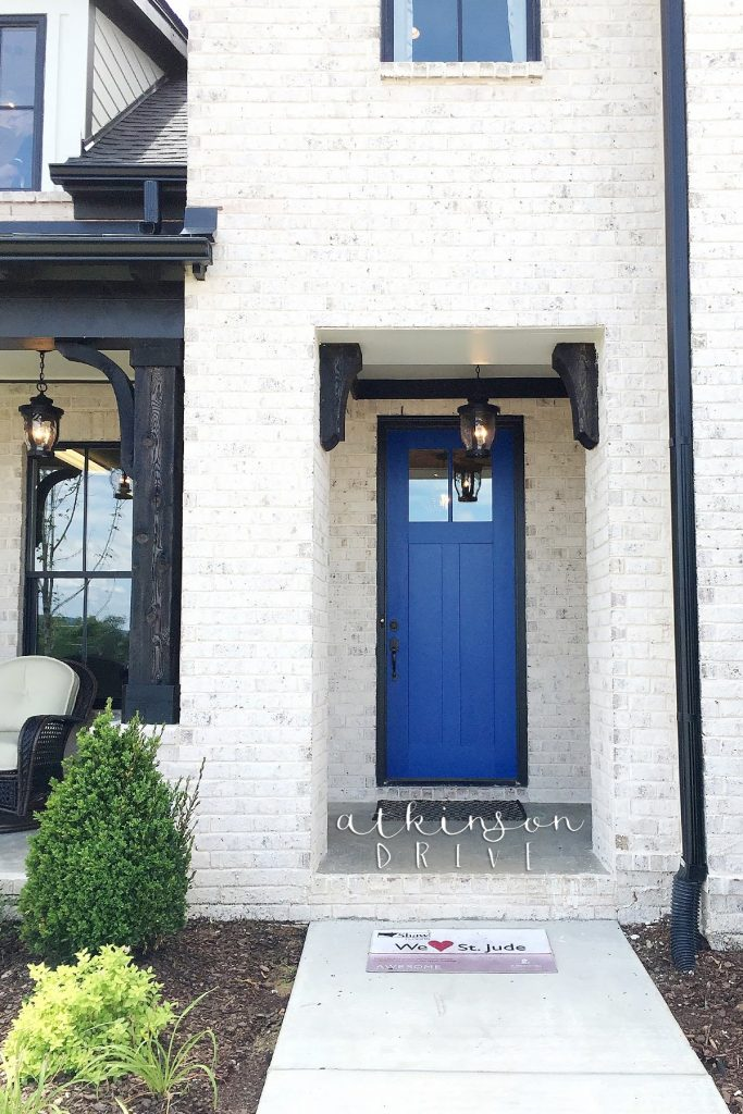 Light brick home exterior with dark wood accents and a bright blue front door
